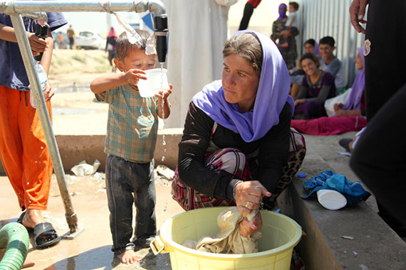 A displaced Yazidi woman washes clothes in a bucket while a boy drinks water from a plastic container at a water point in the Bajid Kandala camp in Iraq, near the border with the Syrian Arab Republic. Photo: UNICEF/Khuzaie