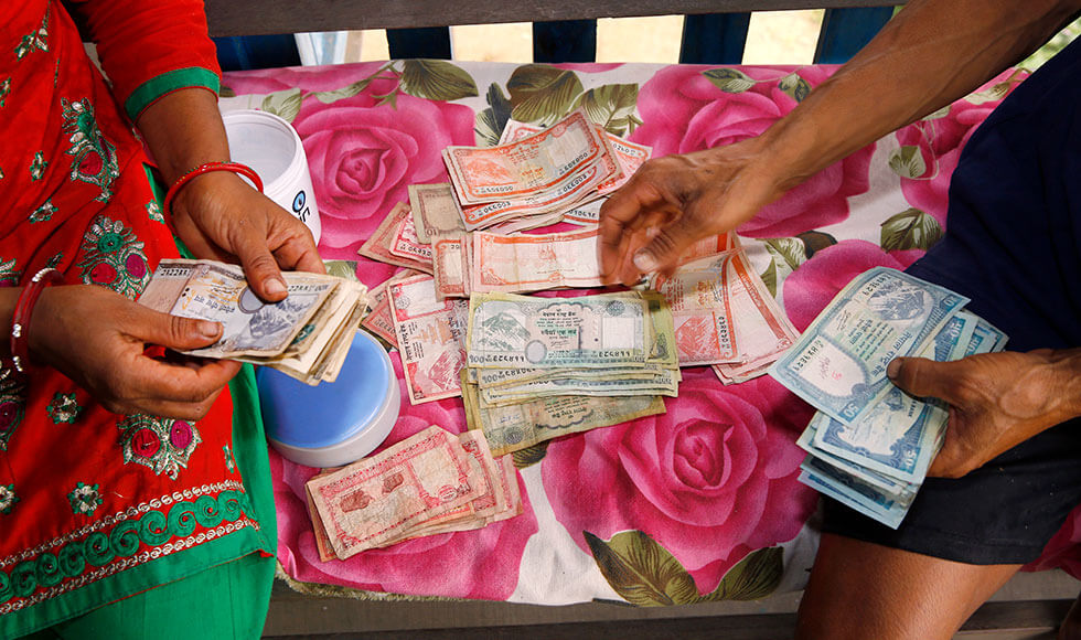 Chandra Kala Thapa and her husband Bir Bahadur Thapa, farmers from Chatiune Village in Sindhuli Disrict, Nepal, count earnings from a recent harvest. Chandra participates in the Rural Women's Economic Empowerment Joint Programme, implemented by UN Women, Food and Agriculture Organization, International Fund for Agricultural Development and World Food Programme, and funded by a consortium of donors, which seeks to improve women farmers' agricultural production and income and change gender-discriminatory attitudes of their male counterparts. Photo: UN Women/Narendra Shrestha.