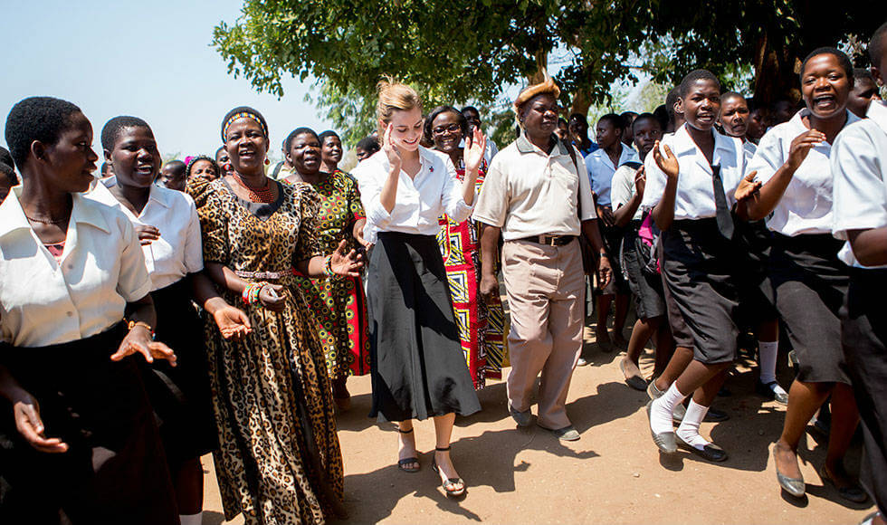 UN Women Goodwill Ambassador Emma Watson (centre) and Senior Chief Inkosi Kachindamoto (left) are welcomed by pupils at the Mtakataka Secondary School, where girls have been able to return to their education after their child marriages were annulled. Photo: UN Women/Karin Schermbrucker.