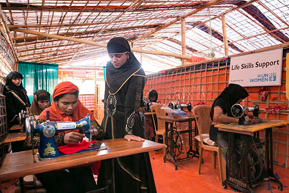 Rohingya refugees like Somjida (standing) have fled desperate conditions, seeking safety at a refugee camp in Bangladesh. They find solace and support by gathering at a Multi-Purpose Women's Centre. Training helps develop skills such as tailoring that can provide new sources of income, along with a sense of returning to stability and a normal life. Photo: UN Women/Allison Joyce.