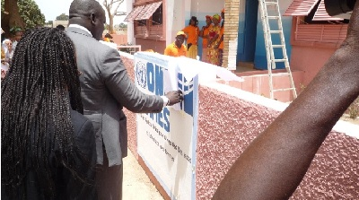 Placing of the UN Women Logo to the wall of the Kullimaaro shelter (Photo Credit: Women/ L. Sanka)