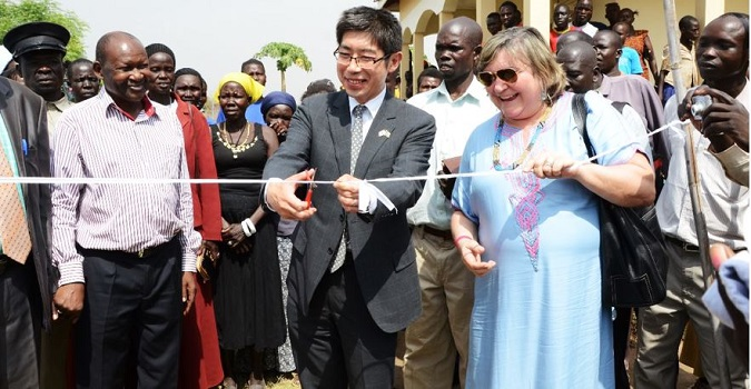 UN Women Deputy Country Representative for South Sudan, The Ambassador of Japan to South Sudan, H.E. Kiya Masahiko and the UN Women Director of Programmes, Ms Maria Noel Vaeza cutting a ribbon as they hand over the resilience building equipment. Photo Credits: UN Women/Rose Ogola