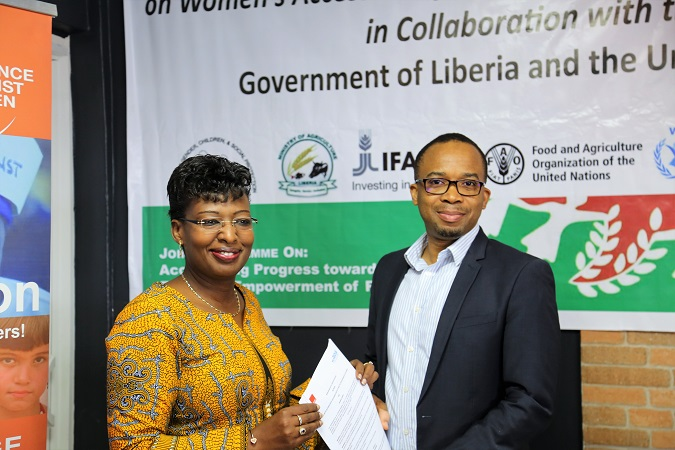 Orange Liberia Chief Financial Officer Mr. Diakalia Berte and UN Women Liberia Country Representative Madam Marie Goreth Nizigama exchange the partnership agreement after signing. Credits: UN Women/Sigrid Valberg
