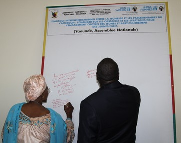 Minister Marie-Therese Abena (MINPROFF) and Minister Mounouna Foutsou (MINJEC) signing the commitment. Photo credit, Teclaire Same, UN Women