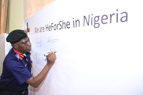 A HeForShe champion signing  the commitment board