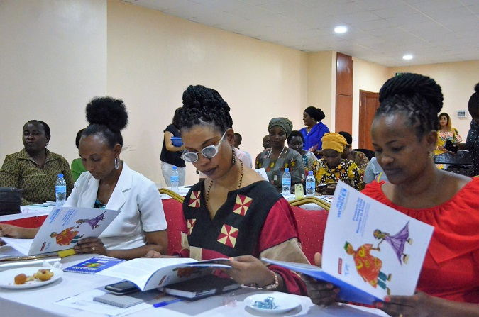 Participants read through the Child Marriage Study report after it was launched in Dodoma on 5 March. UN Women/Tsitsi Matope