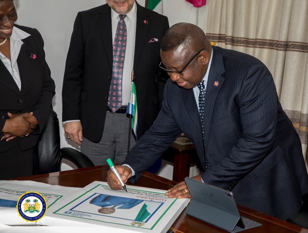 His Excellency Julisus Maada Bio- President of the Republic of Sierra Leone Signing up as HeForShe Champion  flanked by RC-Sierra Leone and UN Women Rep. - State House Sierra Leone 2