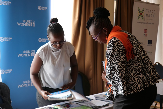 UN Women's Valentine Waroga attends to visitors at the UN Women stand during the event. Photo: UN Women/ Faith Bwibo