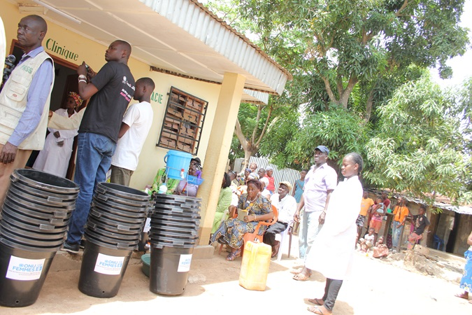In the 5th district of Bangui, representatives of a local NGO follow the precautions for using and bleaching bleach for the washing stations offered by UN Women and the Ministry of Women. Photo: UN Women/Novella Nikwigize