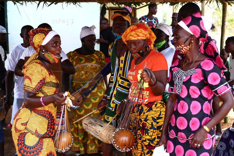 Traditional practitioners in Liberia playing traditional music to welcome guests. Photo credit - UN Women Liberia