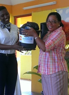 UNFPA Assistant Representative De-Jane Gibbons handing over a dignity kit sponsored by UNFPA and UN Women in the wake of Tropical Storm Erika's impact on Dominica.