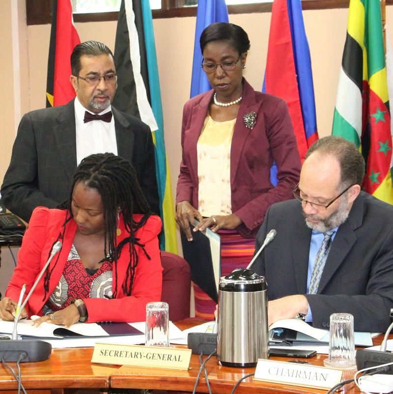 Seated, from left, UN Women Head of Office, Ms. Tonni Brodber, and CARICOM Secretary-General, Ambassador Irwin LaRocque sign the MOU. Standing are Mr. Neville Bissember and Ms. Barbara Vandyke, Office of the CARICOM Secretary-General. Photo compliments of CARICOM