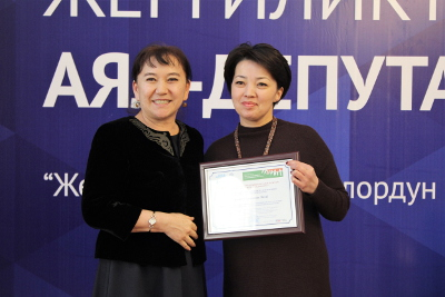 Ainuru Altybaeva, MP- active gender advocate in the Kyrgyz parliament, awarding with a certificate a newly elected woman-deputy of the local council. Photo: UN Women Kyrgyzstan/Meriza Emilbekova