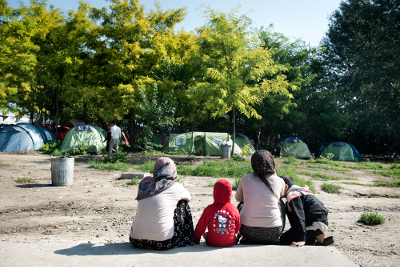 Two women sit with their children at Subotica Transit Centre in Serbia. Photo; UN Women/Ventura Formicone