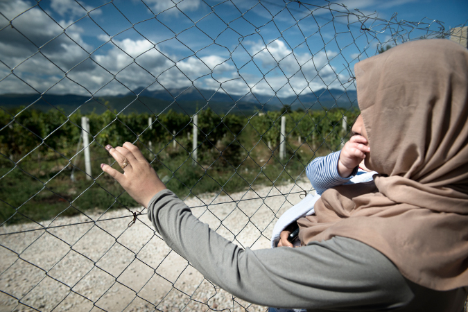 A woman refugee holds her son next to a fence in Vinojug Transit Centre in FYR Macedonia. Photo: UN Women/Ventura Formicone