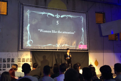Alex Qin on the Main Stage with a Slide Demonstrating Men's Excuses Behind their Actions. Photo UN Women