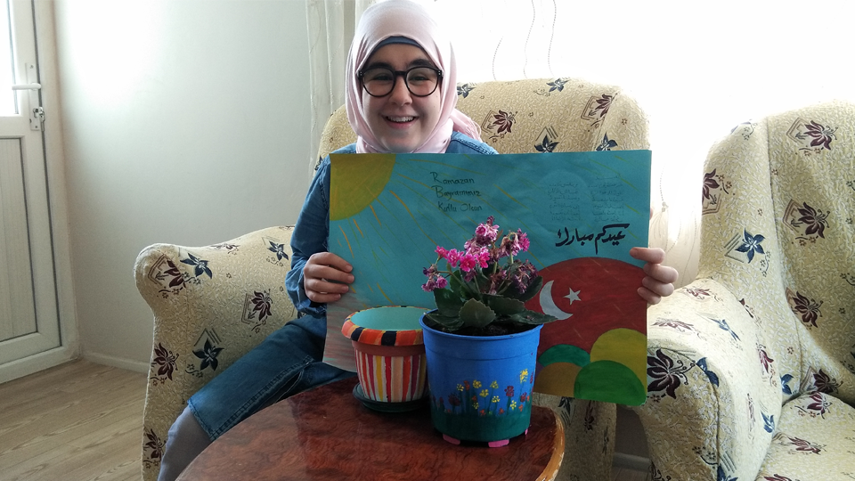A young Iraqi woman Zahraa Hussein Mohsin is holding a drawing with Eid greetings. Photo: From personal archive