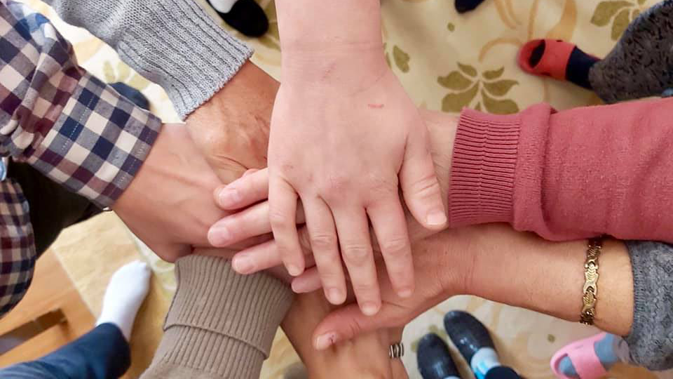 Survivors hold hands after the sessions of psycho-social support. The aim of these sessions was to help women and children actively integrate into the society after tackling the trauma they experienced. Photo: Safe House Gjakova