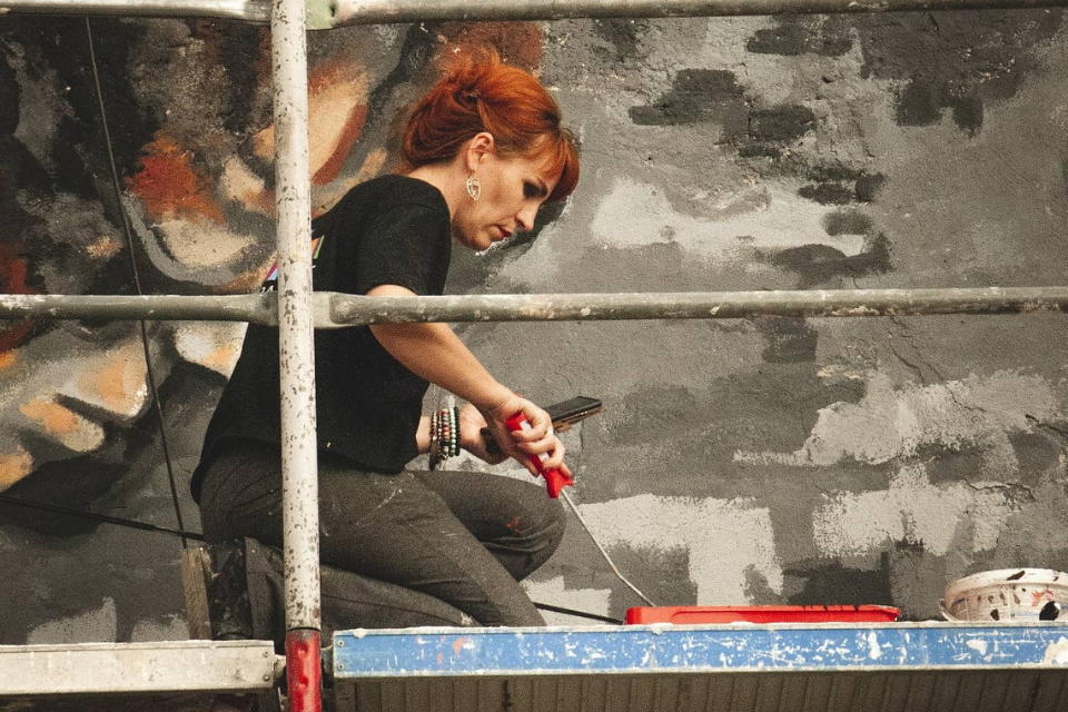 """Artist Lebibe Topalli in the process of painting her mural """"What you sow, you reap"""" in the municipality of Ferizaj, Kosovo. Photo: Donit Avdyli / Mural Fest"""