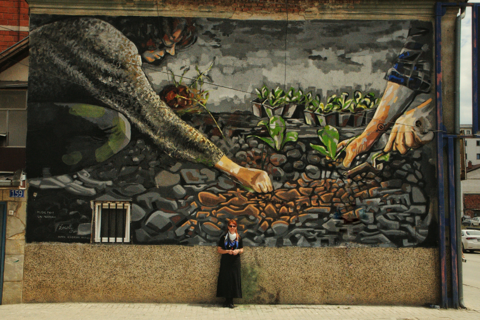 """Lebibe Topalli, in front of her mural """"What you sow, you reap"""" as part of the UN Women regional initiative Mural Artivism; breaking the walls of gender inequality. Photo: Donit Avdyli / Mural Fest"""