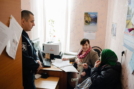 Together with the local social assistant, police officer Victor Zglavoci talks to an elderly woman from the village, Colibasi, Moldova. Photo: UN Women/Ramin Mazur