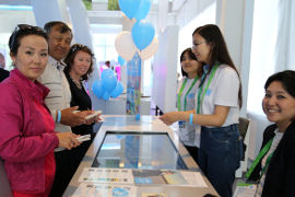Visitors at UN Women booth at EXPO 2017 supporting gender equality. Photo: UN Women/Aijamal Duishebaeva