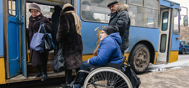 Tetyana Bobrovska waits for a city bus in Kramatorsk, Ukraine. In Kramatorsk, many older buses and bus stop shelters are inaccessible to wheelchair users. Photo: UN Women/Artem Hetman