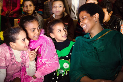 UN Women Executive Director Phumzile Mlambo-Ngcuka laughs with a group of young girls during a visit to one of UN Women's Cairo Safe City programme sites on 3 February 2015. UN Women Egypt /Mohamed Ezz Aldin