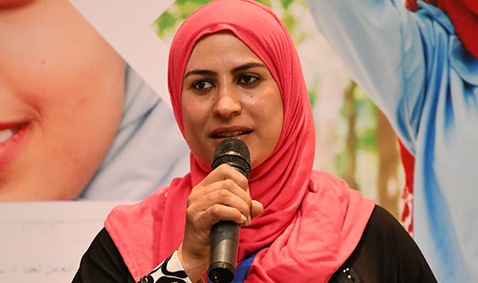 Samar Hamdy sharing her story during a Conference on Women Employment Promotion Programme Achievements