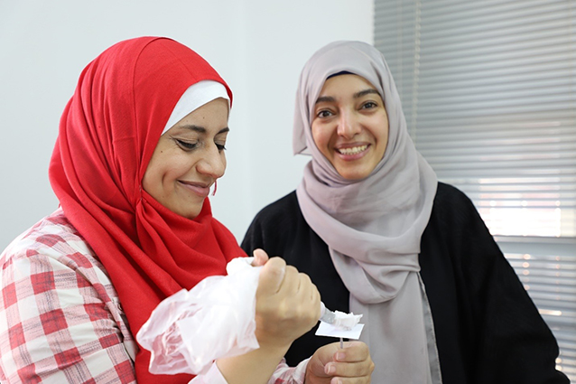 Etemad (right), a Yemeni refugee taking part in the LEAP programme, learns how to make sugar flowers for cake decorating. Photo: UN Women/Nada Ismail