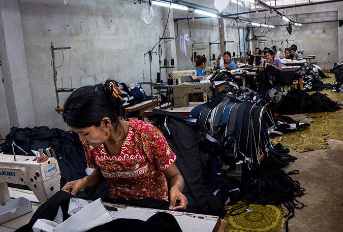 Burmese migrant workers sew clothes in a factory in Thailand's western province of Mae Sot. Their working day runs from 7 am until 8 pm, including overtime, for which they earn less than 200 baht (6 dollars), well below the legal minimum wage of 305 baht. Their monthly income barely covers rent and food, leaving little opportunity for saving and reducing them to living day-to-day. Photo: UN Women/Piyavit Thongsa-Ard
