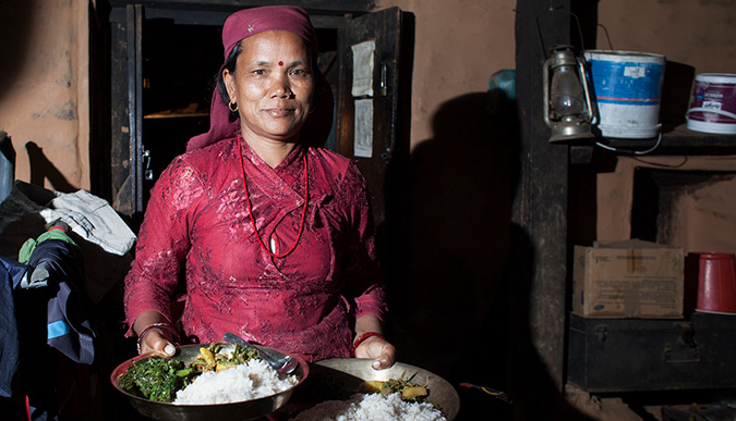 Puspa Kumari Gurung, running a home stay in Lwang Gaon, Nepal, serves dinner to the guests- a traditional Nepali thali that includes a chicken curry, spinach, lentils, potatoes, rice and chutney.   Photo: Vidura Jang Bahadur