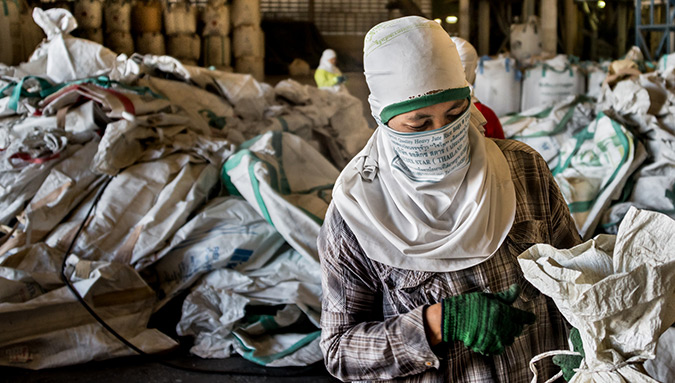 A Burmese worker handles empty sacks at a rice mill in Ubon Ratchathani province. The sacks are returned  at a rate of several hundred per day to the mill, where workers sort, clean and repair them for re-use.  Photo: UN Women/Piyavit Thongsa-Ard