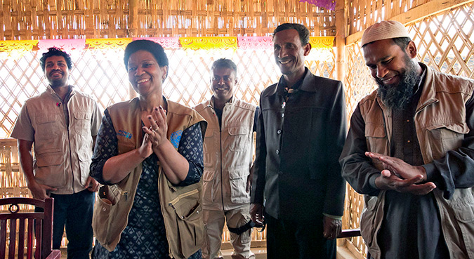 "UN Women Executive Director, Phumzile Mlambo-Ngcuka  pins ""He For She"" pins on CIC's in charge of camps, Shamimul Huq Pavel, Muhammed Talut, and ASM Obaidullah in Balukhali Rohingya Refugee camp February 1, 2018 in Chittagong district, Bangladesh.   Photo: UN Women/Allison Joyce"