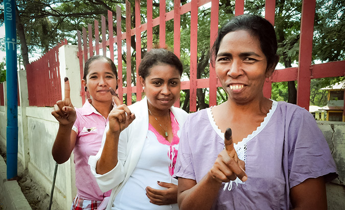 Youth voters dip their fingers into the indigo-blue dye. Photo: UN Women/Betsy Davis Cosme