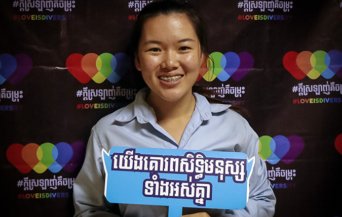 "Srong Seavmey, 21, holding up the message, ""We all respect human rights,"" at the LOVEISDIVERSITY media platform launch at Pannasastra University of Cambodia on 8 June. Photo: UN Women/Sreynich Leng"