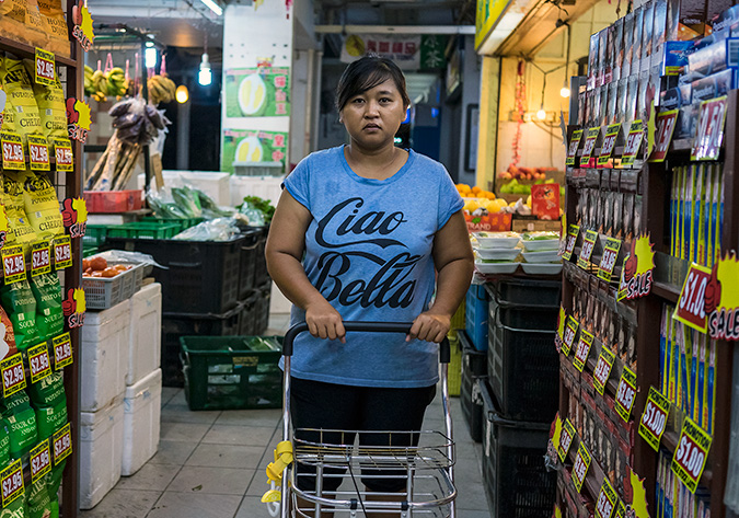 Nurachayatun Siti, a 35-year-old Indonesian domestic helper from Surabaya Java, does the family shopping early Saturday morning, 25 November 2017, in Sembawang Hills Estates, Singapore. This is Nur's second job as a domestic worker in Singapore. The first when she was 19, was a painful and demoralizing situation where her employers had her sleep on the floor for two years, with little food, no time off, and S$20 per month, the rest of her wages were either withheld or taken by the agency that placed her. The end came when her employer accused her of theft. She gladly left. This time she has returned on her own terms earning well about the average $550. On her one day off, Nur is learning how to sew, meets with friends, and attends labour law discussions to better protect herself.  Photo: UN Women/Staton Winter