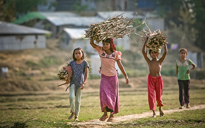 Girls carry firewood in Balukhali camp March 5, 2018 in Cox's Bazar, Bangladesh. Photo: UN Women/Allison Joyce