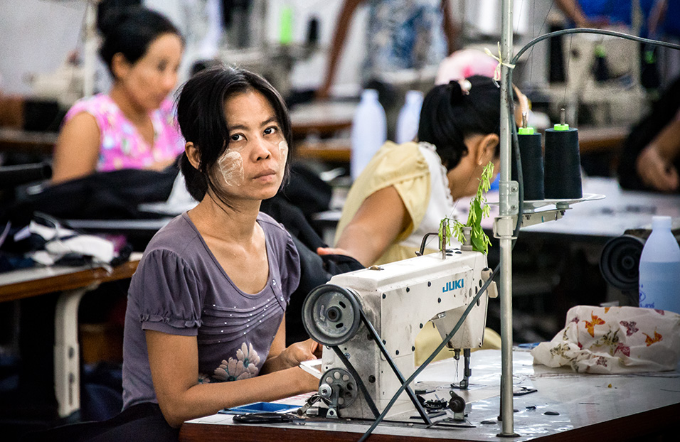 Myanmar migrant workers sew clothes in a factory in Thailand's western province of Mae Sot. Their working day runs from 7 am until 8 pm, including overtime, for which they earn less than 200 baht (6 dollars), well below the legal minimum wage of 305 baht. Their monthly income barely covers rent and food, leaving little opportunity for saving and reducing them to living day-to-day. This limited income security compounds other challenges that they face such as limited protections in housing, labour contracts and healthcare. Photo: UN Women/Piyavit Thongsa-Ard