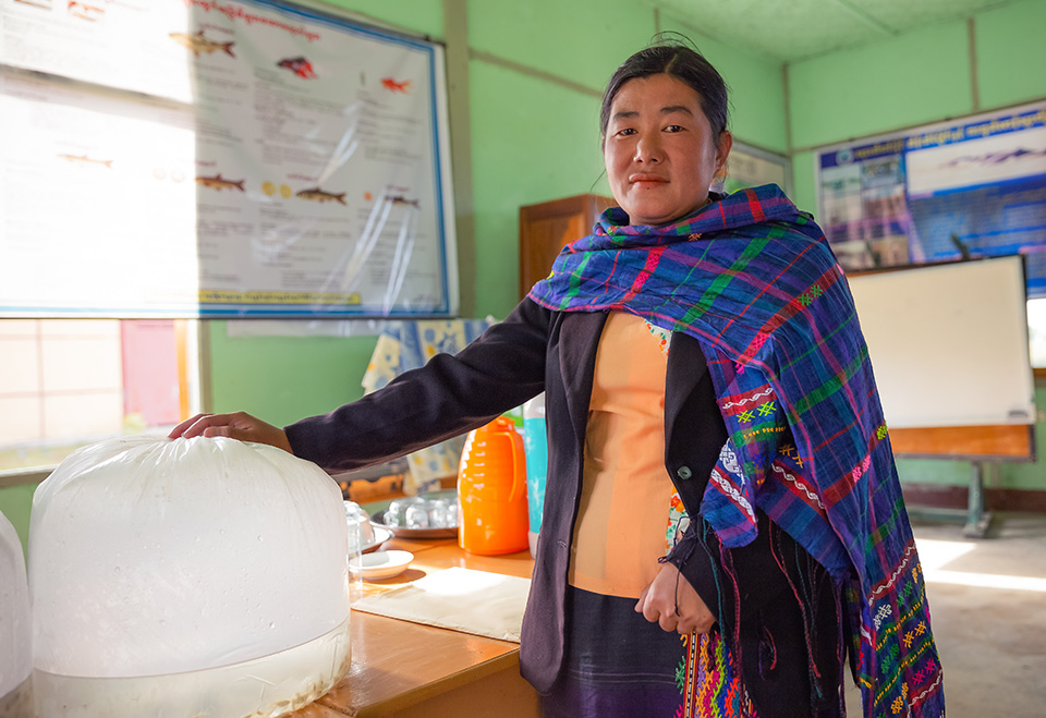 In Hka Shi village, Waingmaw township, a woman enrolled in the catfish farming training says she is thankful she can do it from home, while caring for her baby. Photo: UN Women/Stuart Mannion