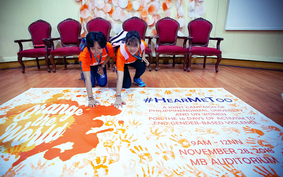 Students print their palms in orange at a 28 November ceremony at Philippine Normal University to express their commitment to speak out against sexual harassment. Photo: UN Women/Norman Gorecho