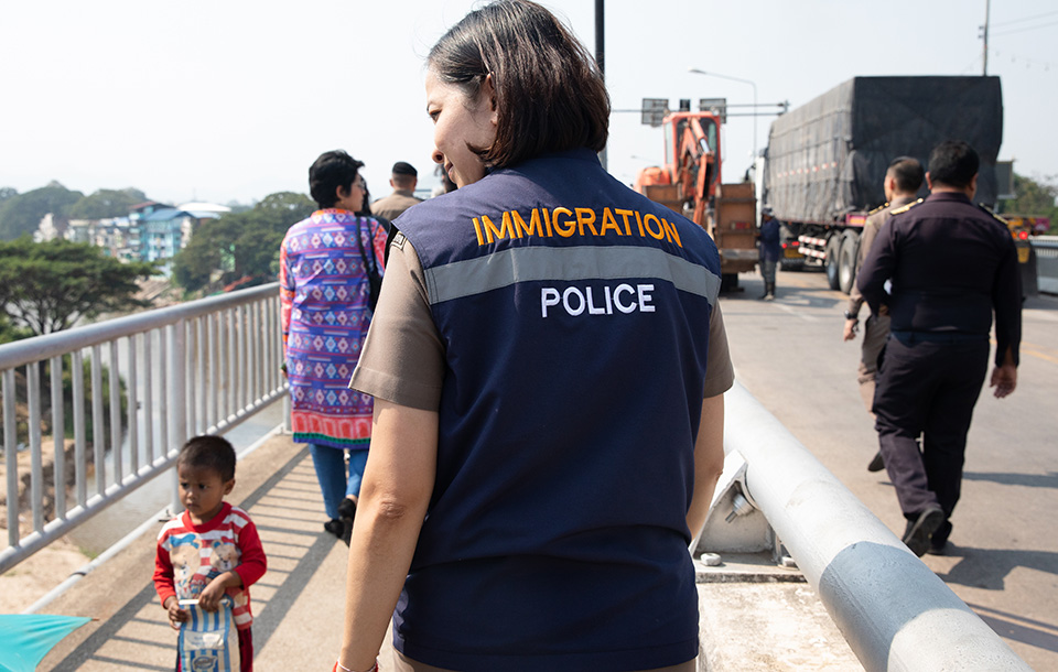 A female immigration officer stands on the Thai-Myanmar Friendship Bridge I. Photo: UN Women/Stephanie Simcox