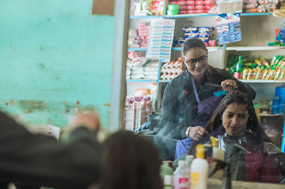 Timalsina runs her beauty parlour alongside her grocery store. At times a comical contrast, the two units coexist in one space. Photo: UN Women/Merit Maharjan