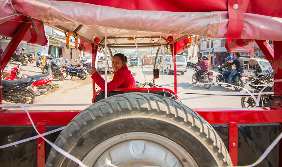 Padma Chaudhary waits for passengers in Dhangadhi bazar. She says she used to feel uncomfortable when she first started, but now feels confident about her skills as a driver. Photo: UN Women/Merit Maharjan