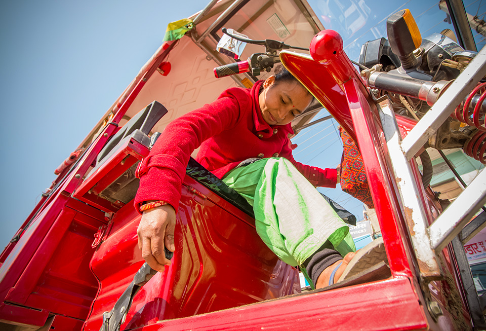 Padma Chaudhary prepares to start her day after taking her e-rickshaw out from a rented shed in Dhangadhi bazaar, where she parks it at night before returning home to Phulwari. Photo: UN Women/Merit Maharjan