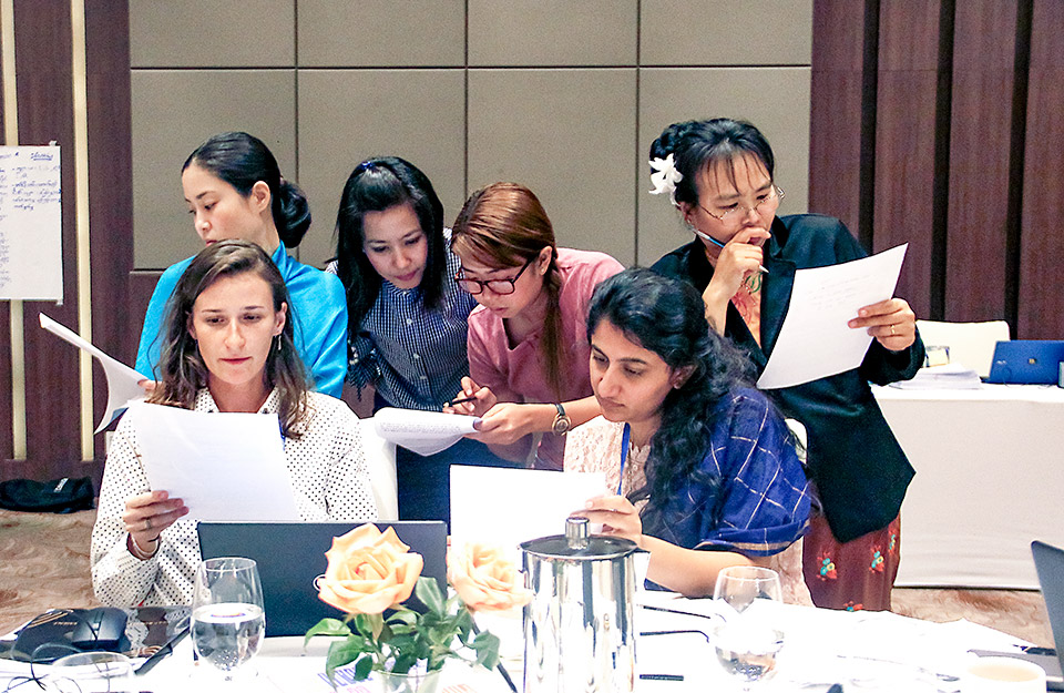 Participants absorbed in group work to build their own training modules. Photo: UN Women/Cecilia Truffer