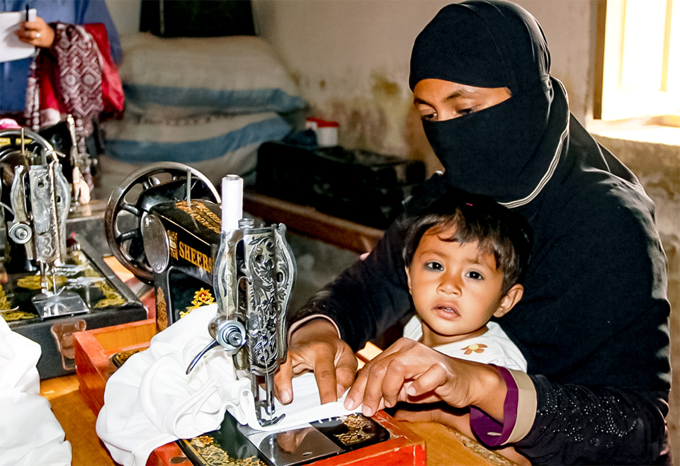 Salma works on sewing machine at Community Center in Gharo, while her son looks on. Photo: UN Women/Habib Asgher