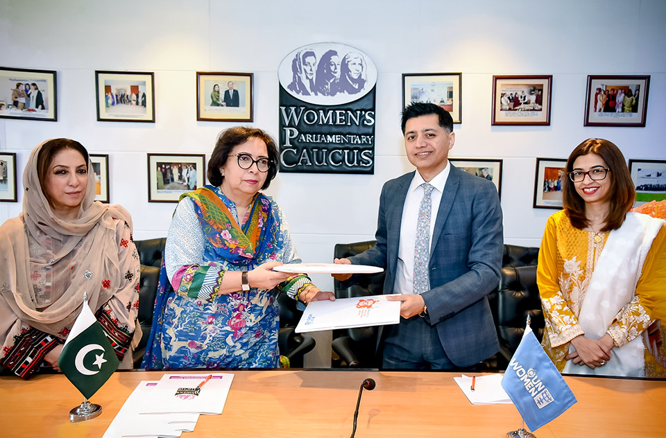 WPC Secretary Munazzah Hassan and UN Women Country Rep Jamshed Kazi exchange documents after signing MoU at National Assembly. Photo: UN Women/Habib Asgher