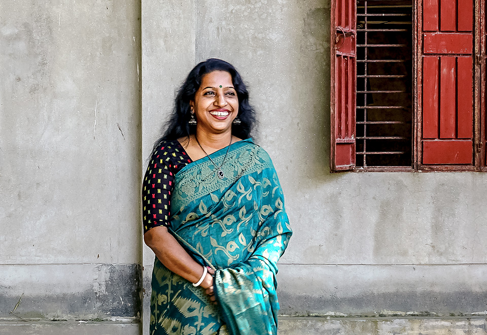 Sarothi Rani Saha smiles in the courtyard of her Rangpur, Bangladesh-based NGO.  Photo: UN Women/Tasfiq Mahmood