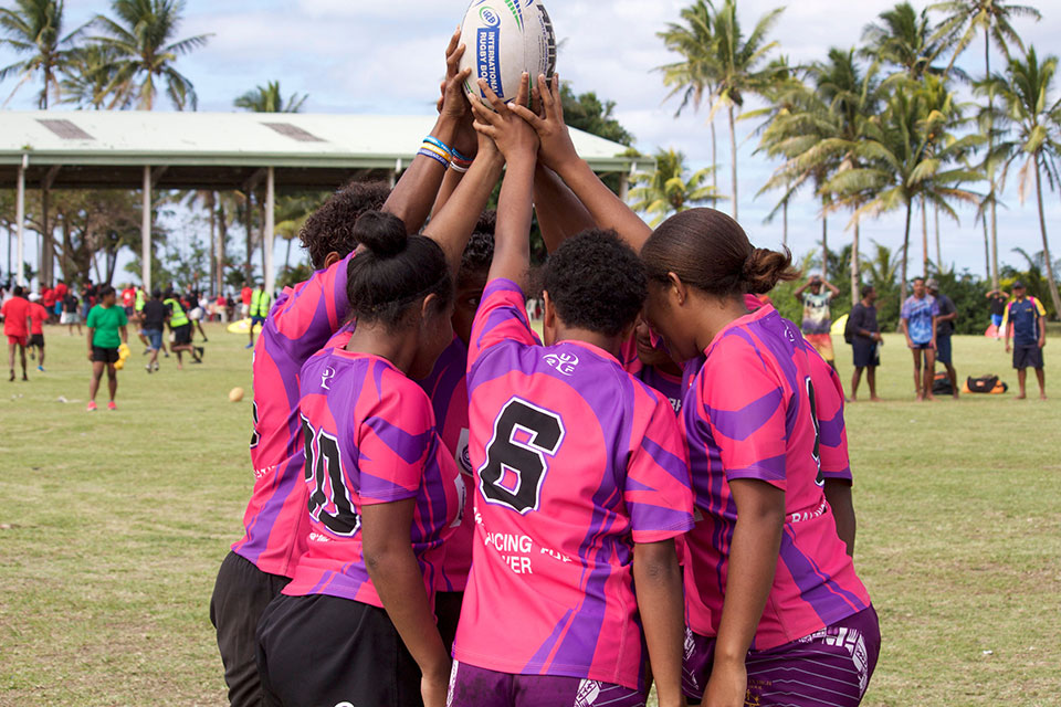 A group of girl rugby players huddle in Fiji. Photo: Oceania Rugby